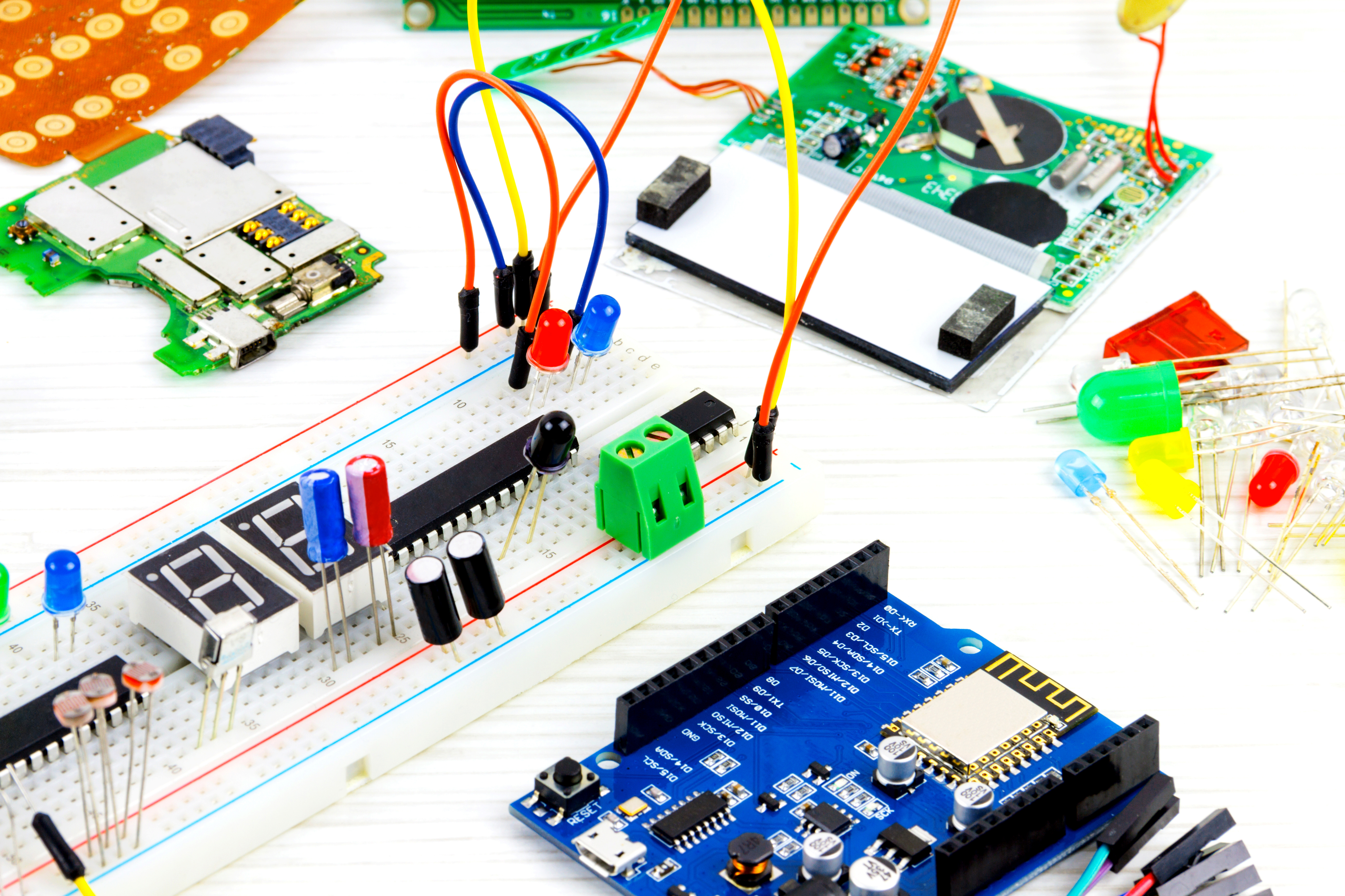 Microcontrollers, chips, resistors and light-emitting diodes on white desktop of hardware engineer. Engineer workplace